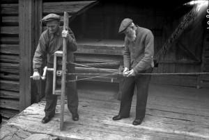 Fra Hadeland Folkemuseum. To eldre menn fletter et tau.